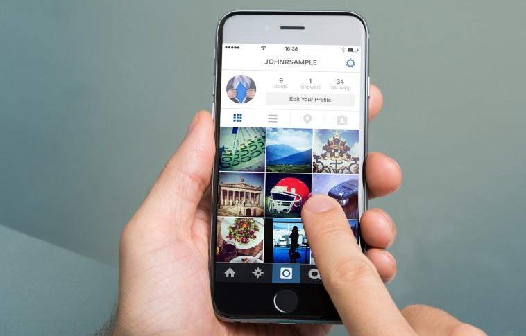 bigstock-hand-using-instagram-on-apple-74053759-758x485